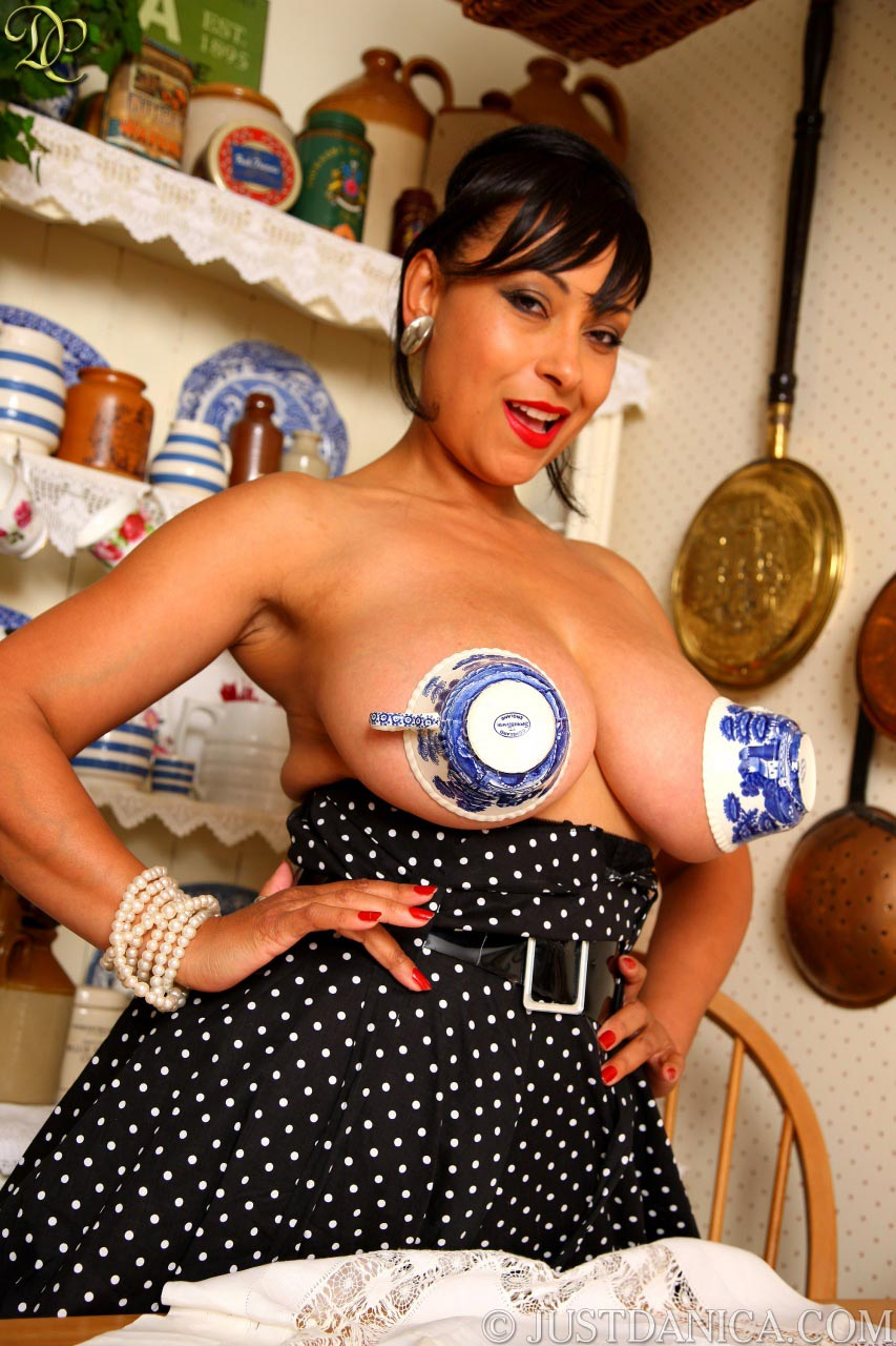 Beautiful MILF uses a couple of tea cups as a bra for her enormous boobs