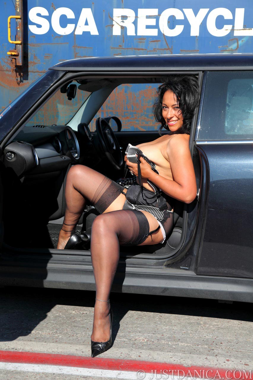 Classy lady is undressing whule sitting on a passenger seat of the car