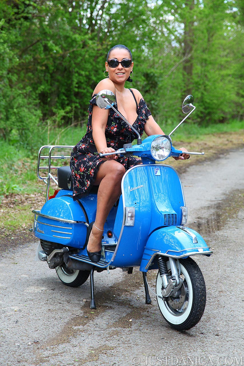 Danica Collins posing on top of vibrating Vespa scooter