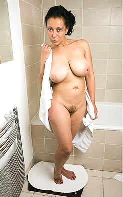 Nude mature woman drying herself