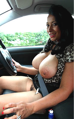 Car drives with pair of massive tits exposed